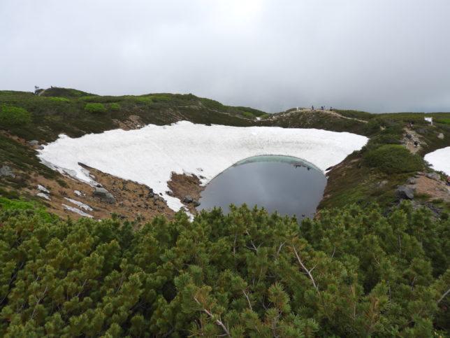 残雪の中のすり鉢池